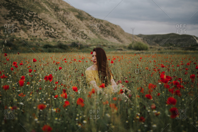Pensive attractive red haired adult lady in yellow dress with red poppy in hair and red lips looking away while sitting alone in blurred amazing green meadow