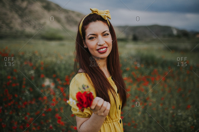 Smiling attractive red haired adult female in yellow dress and headband with red lips holding bouquet with red rose