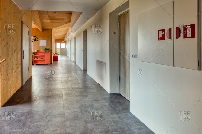 Clean cozy light corridor with wooden and white walls and gray tile floor in modern spacious lobby of hotel meeting all international hospitality standards