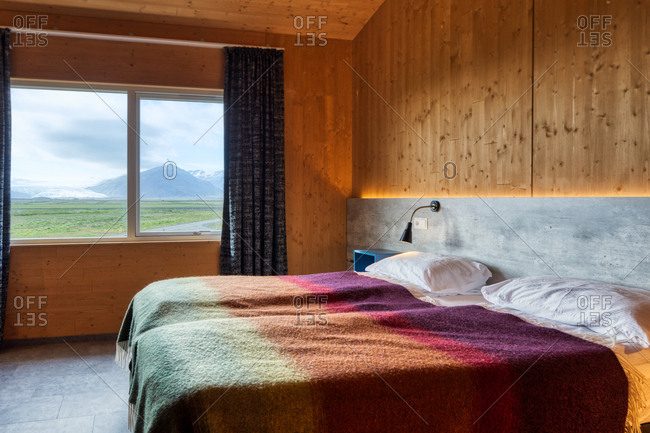 Two neat comfortable beds with white pillows and warm colorful blankets in light cozy room with yellow walls against window with blue curtains overlooking rural landscape