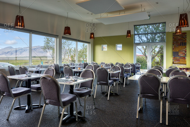 Neat empty cozy light hotel canteen with comfortable furniture on first floor near parking with windows overlooking blurred green meadow and snowy mountains