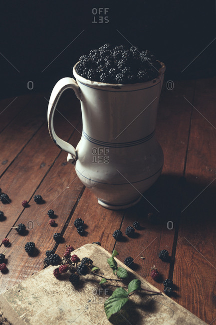 Vintage jag with ripe blackberries on wood and leaves on a old book