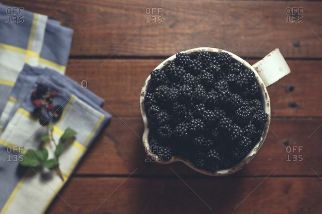Vintage jag with ripe blackberries on wood