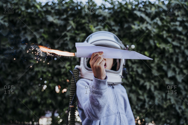 Excited boy in astronaut helmet playing with paper plane with petard in garden