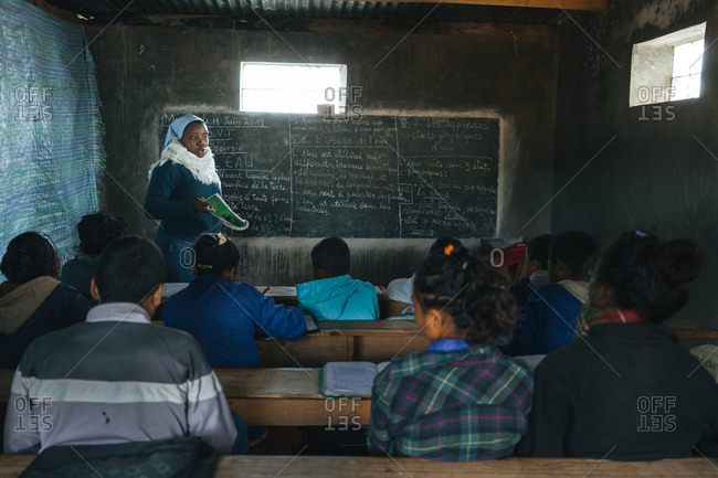 Madagascar - JULY 6, 2019: African teacher standing by blackboard and speaking to pupils in class divided by fabric curtain in weathered old school building