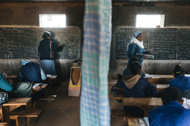 Madagascar - JULY 6, 2019: African teachers standing by blackboard and speaking to pupils in class divided by fabric curtain in weathered old school building