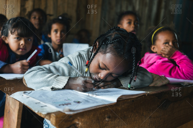 Madagascar - JULY 6, 2019: Attentive African children listening and writing in notebooks while sitting at desks in rural school
