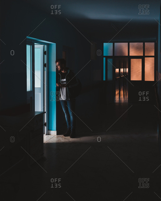Madagascar - JULY 6, 2019: Curious man in casual clothes standing and leaning on wall by doorway in dark hallway