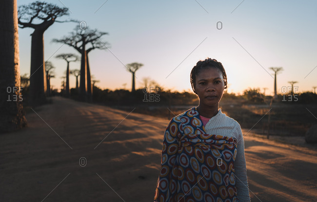 Madagascar - JULY 6, 2019: Confident ethnic woman in exotic multi colored outfit standing at slope by tall baobab trees in sun rays at twilight