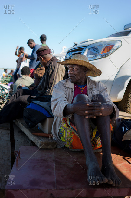 Madagascar - JULY 6, 2019: Barefoot black man in hat and aboriginal outfit sitting on weathered boards by parked car next to casual people in daylight