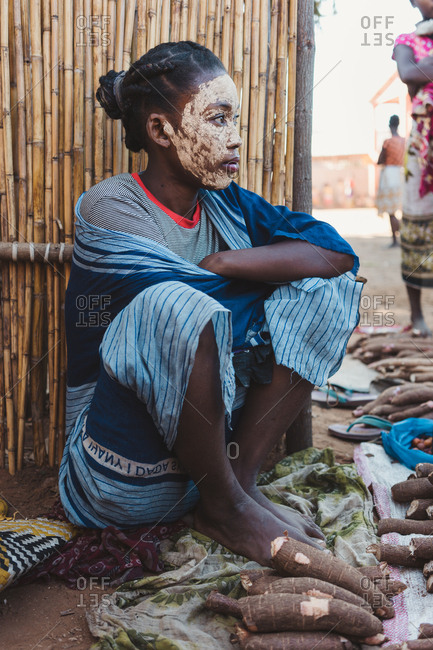 Madagascar - JULY 6, 2019: Exotic ethnic person in multi colored modern outfit sitting by fence and selling piles of edible root vegetable
