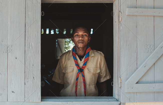Madagascar - JULY 6, 2019: Serious black man in uniform with colorful scarf standing by window with wooden shutters