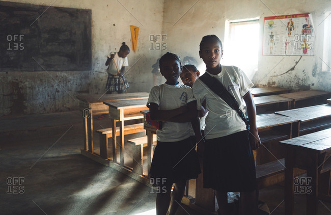 Madagascar - JULY 6, 2019: Interested black girls in uniform looking at camera and standing by desks in raddled class in rural school