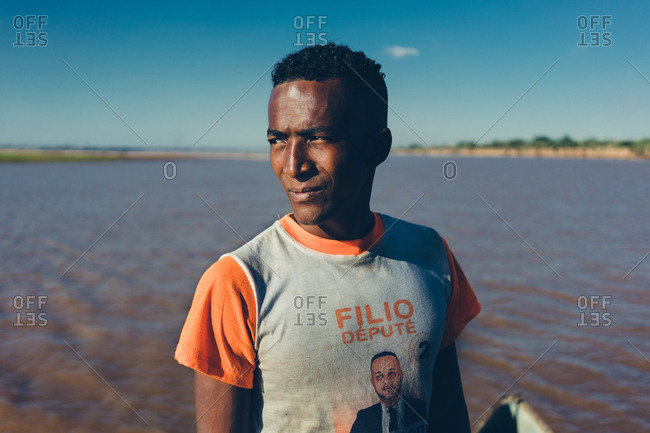 Madagascar - JULY 6, 2019: Squinting ethnic man in casual outfit standing by waterfront on sunny day