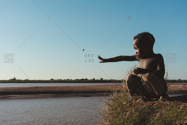Madagascar - JULY 6, 2019: Neutral black child throwing stones into water while squatting at summer river bank