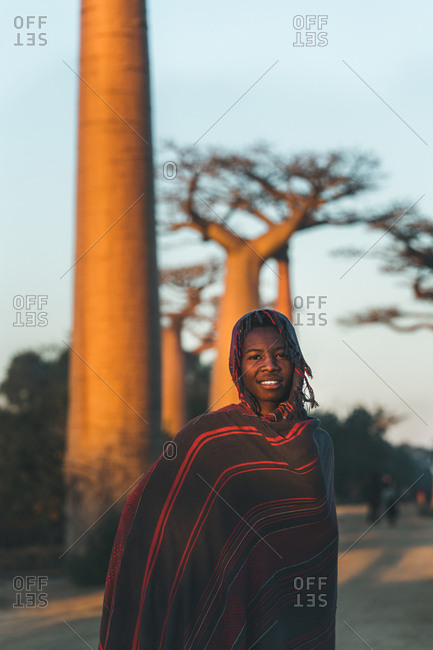 Madagascar - JULY 6, 2019: Content African woman in exotic multi colored cover with hood standing by baobab trees in sun rays at twilight