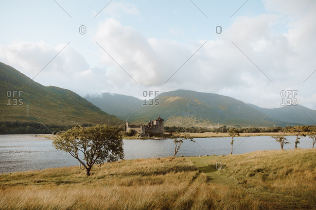 Damaged old castle located on coast of calm lake against grassy hills on cloudy day in UK countryside