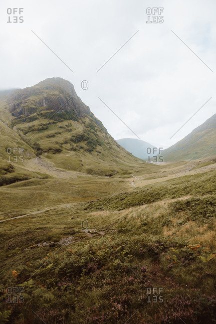 Picturesque view of green valley by high rocks in Glencoe on daytime