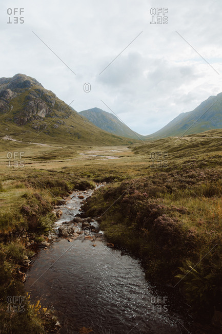 Tranquil landscape with high rocks green grass and small river under cloudy sky on Glencoe