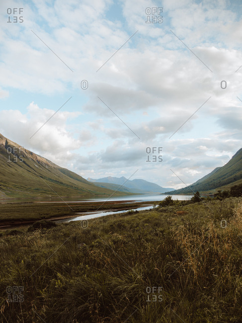 Idyllic landscape of high green mountains and valley with tranquil river under cloudy sky in Glen on summertime
