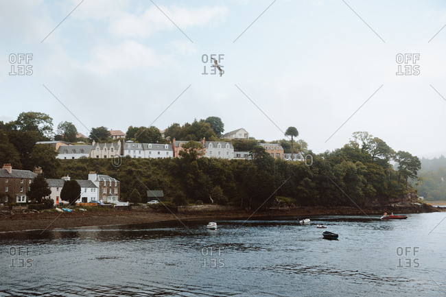 August 10, 2019: Gloomy landscape of different houses and trees on hill by water with sailing boats in Portree under cloudy sky