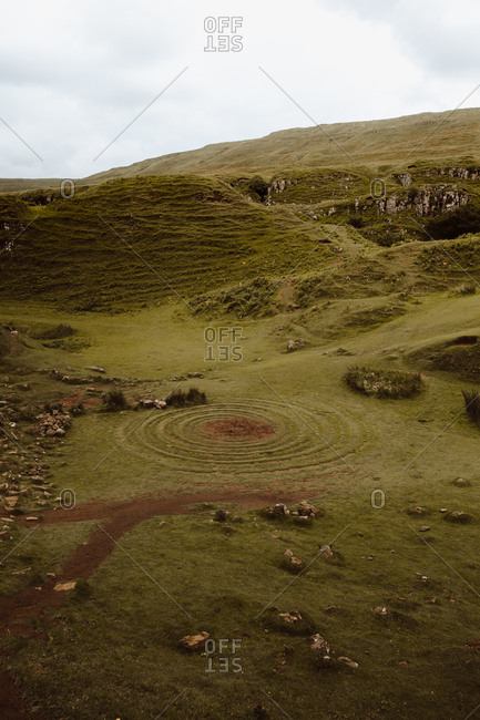 Mountain valley covered with green grass and mysterious spiral labyrinth made of stones in Fairy Glen