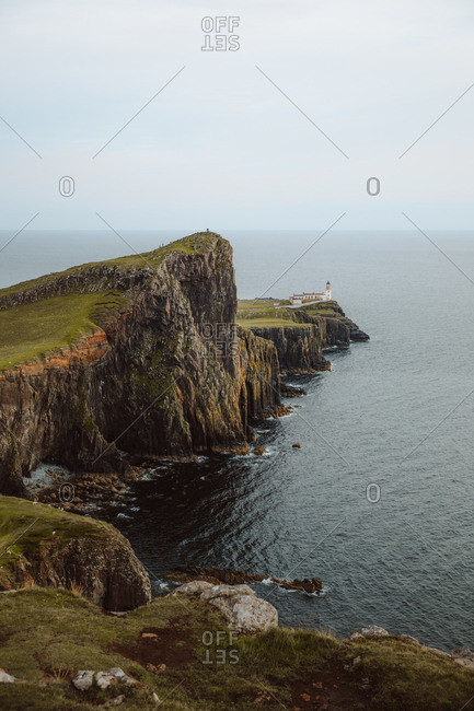 From above majestic view of Neist Point Lighthouse built on high rocks surrounded by dark water on daytime