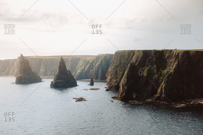 From above breathtaking landscape of cone shaped rock formations in water by coast in Duncansby Head on sunny day