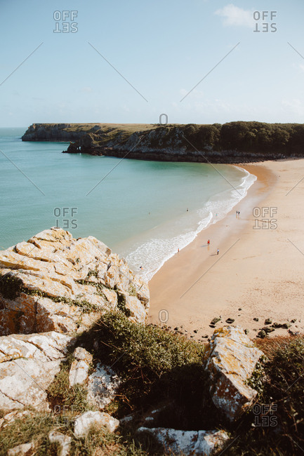 Idyllic view of green water deserted seashore and bare rocks in Barafundle Bay on sunny day