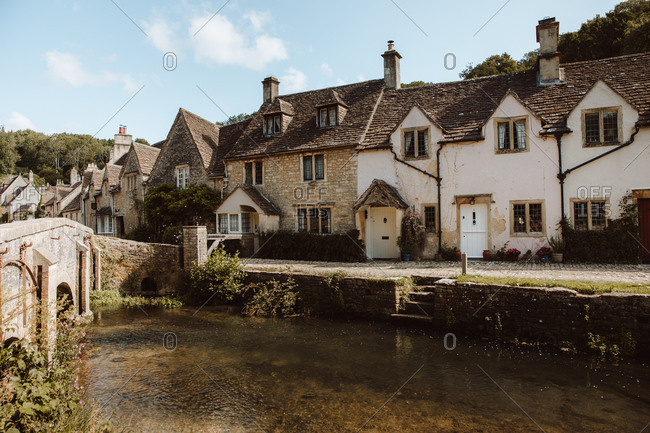 August 20, 2019: Picturesque view of medieval village Castle Combe with white and gray stone buildings by river in Dorset, England on sunny day