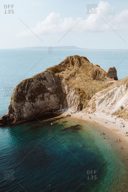 From above idyllic seascape with rocks called Durdle Door and people relaxing on seashore on summer day