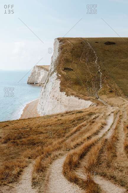 Picturesque view of blue sea and white chalk stone rocks with wheel track on grass near Durdle Door on daytime