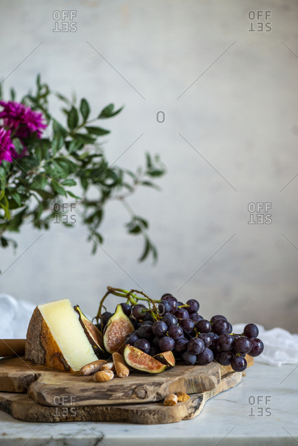 Sliced ripe figs and dark blue grapes next to piece of cheese on wooden cutting boards near bouquet of pink flowers among green leaves against blurred gray wall