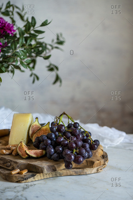 apes next to piece of cheese on cutting boards near pink flowers