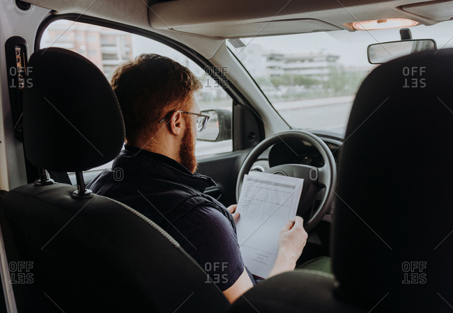 Back view of attentive thoughtful adult man focusing and checking documents while sitting behind steering wheel in car cabin during daytime on blurred background
