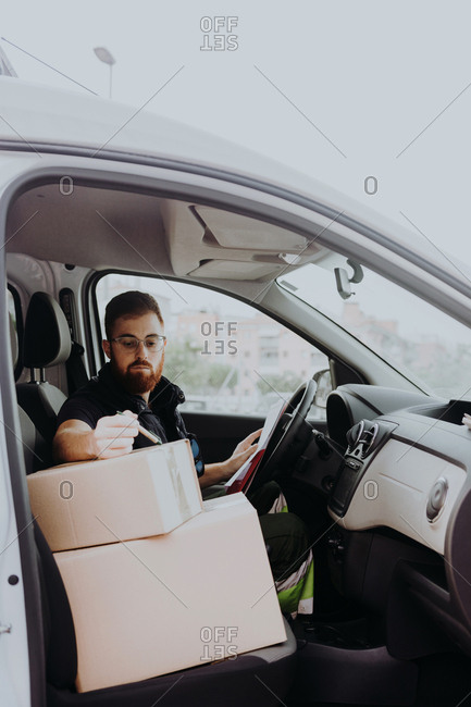 Attentive adult bearded courier in glasses preparing packages for transportation while sitting and marking boxes in car on blurred background during daytime