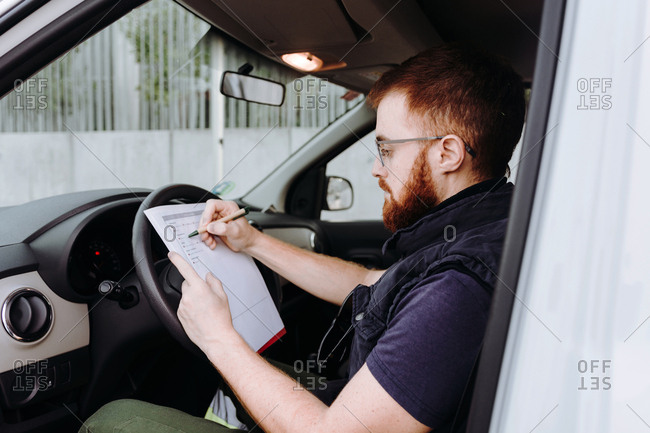 Side view of attentive thoughtful adult man focusing and checking documents while sitting behind steering wheel in car cabin during daytime on blurred background