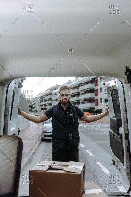 Attentive adult bearded courier in glasses carefully unloading cardboard boxes from car for further delivery to customer on blurred background during daytime