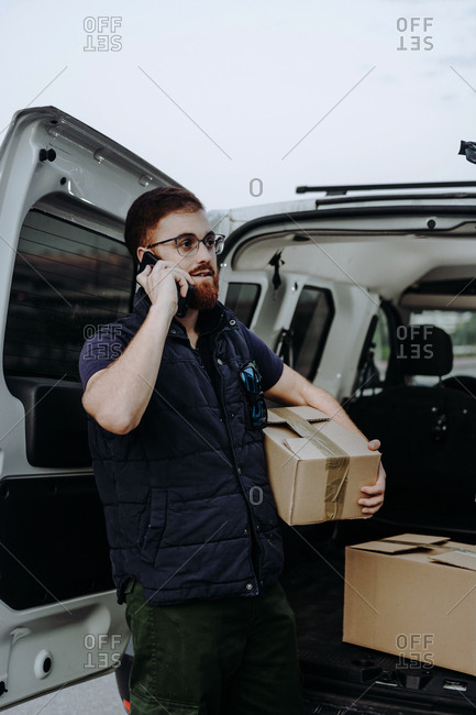 Pleased adult bearded courier in glasses holding boxes and making warning call to customer for further delivery while standing near car trunk and looking away during daytime