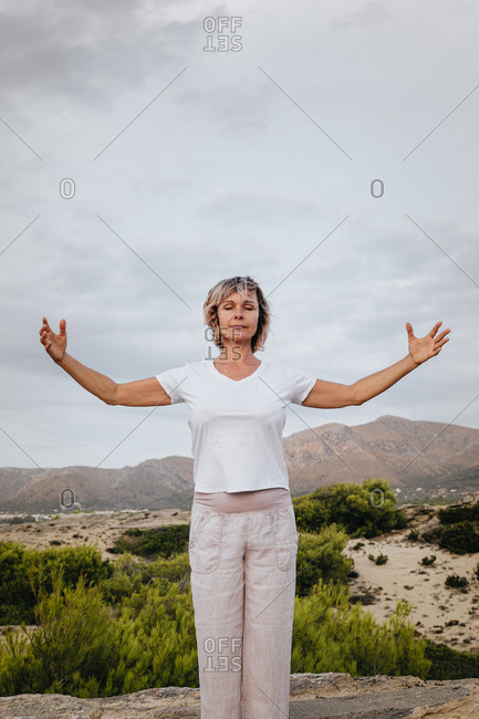 Full body barefoot adult female clasping hands over head and closing eyes while standing on rock in nature and meditating