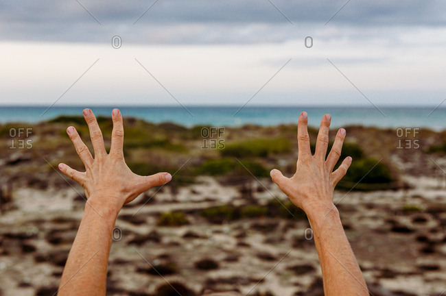 Unrecognizable person stretching out hands while practicing Tai Chi on blurred background of countryside