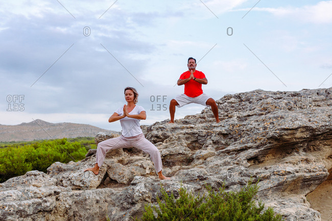 Adult man and woman with closed eyes and clasped hands standing on rough stone and meditating while practicing Tai Chi against overcast sky