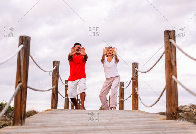 Couple practicing martial arts on lumber path