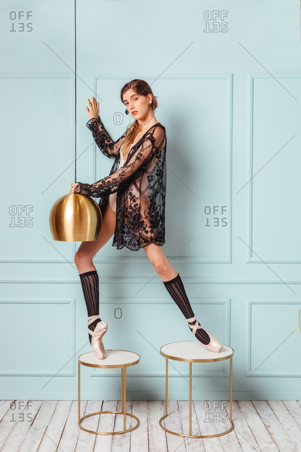 Ballet girl posing next to a golden lamp on a turquoise background.