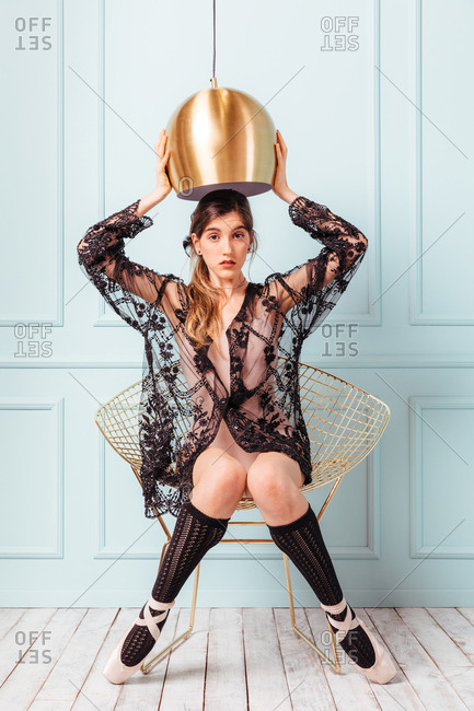 Sensual graceful woman in black lace wearing and knee-highs sitting on chair holding lampshade and looking at camera