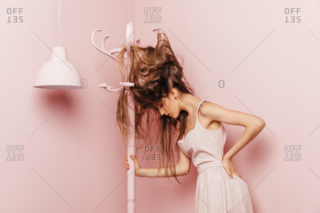 Front view of a teenage girl with tangled hairs on pink background