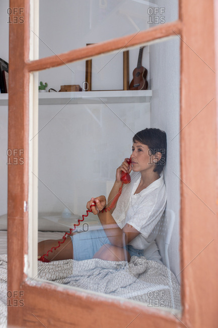 Young female and answering phone call from vintage red telephone while sitting on bed in cozy bedroom throughout glass