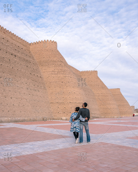 Back view of ethnic man and woman embracing each other and looking on shabby walls of ancient fortress on cloudy day in Bukhara, Uzbekistan