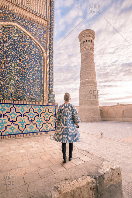 Back view of female in ornamental coat standing on aged square against cloudy sky in Bukhara, Uzbekistan