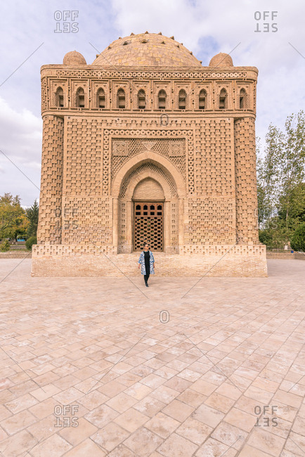 Female walking on pavement outside ancient traditional building during trip in Bukhara, Uzbekistan